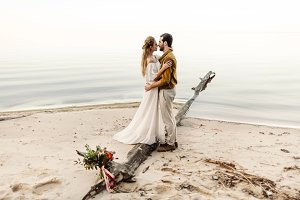 A beautiful couple is embracing on the sea background. Moment before the kiss. Romantic date on the beach. Wedding. Artwork