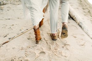 A young couple is walking on the sea coastline. Close-up image of legs. Artwork