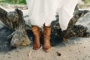 Girl in stylish brown boots stand on the beach next to the stump. Close-up image of legs. Artwork. Wedding concept