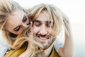 A young couple in love having fun and playing with a hair of the girl. A cheerful bride and groom laughing, close-up. Artwork