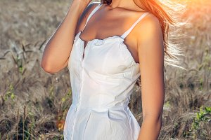 Girl in a white dress field, wheat smile happiness, beautiful hair glare of the sun.