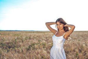 Girl in a white dress field, wheat outdoor recreation, beautiful dress. Woman posing outdoors in long hair. Close-up