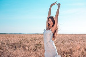 Girl in a white dress field, wheat outdoor recreation, beautiful dress. Woman posing outdoors in long hair. He pulls his hands in the sky