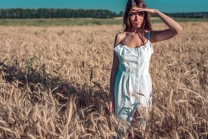 Girl in a white dress field, wheat outdoor recreation, beautiful dress. He looks out into the distance, his hand is covered by the sun.