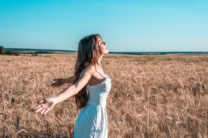 Girl in a white dress field, wheat outdoor recreation, beautiful dress. Hands open in the sides meets the dawn, the sunset.