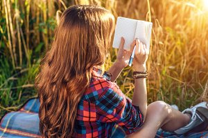 Girl sitting in a field shirt, wheat relaxing on nature, beautiful hair. Writes ideas in a notebook. A student after school. Concept notes.