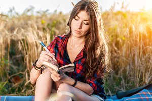 Girl sitting in a field shirt, wheat relaxing in nature, beautiful brunette hair. Writes ideas in a notebook. A student after school. Concept notes.