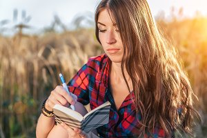Girl sitting in a field shirt, wheat relaxing in nature, beautiful brunette hair. Writes a notepad of the idea. A student after school. Concept of plans for the future.