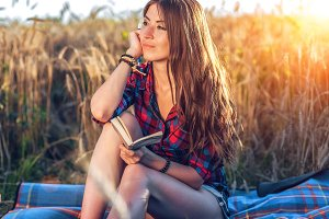 Girl sitting in a field shirt, wheat relaxing in nature, beautiful brunette hair. The notepad of idea is dreaming. A student after class. Concept of plans for the future.