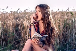 Girl sitting in a field shirt, wheat relaxing in nature, beautiful brunette hair. Eats an apple, notepad pnany for the future. A student after class.