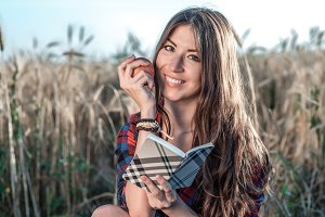 Girl sitting in a field shirt, wheat relaxing in nature, beautiful brunette hair. Holds an apple, notepad pnany for the future. Happy smiling looking in frame.