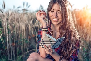 Girl sitting in a field shirt, wheat relaxing in nature, beautiful brunette hair. Holds an apple, notepad pnany for the future. Happy smiling. The concept notes are lessons for the interview.