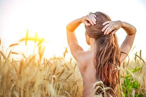 A girl in the field adjusts her hair, a naked torso, a brunette woman with long hair. Wheat field, the idea of hair care. Healthy hair hands nature.