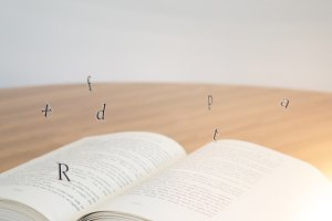 Floating letters on book.