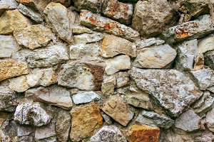 Stone old wall from huge blocks. Background of stones. The concept reliability. The space between stones is filled with cement.