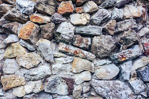 Stone old wall from huge blocks. Background of stones. The concept of reliability. Beautiful textured vintage antique background.