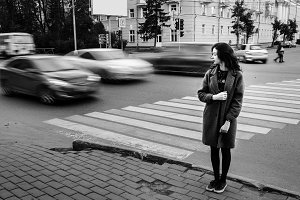 One teenage girl blue coat standing at the traffic light on city street on a cloudly autumn day with vehicles passing by in motion blur.