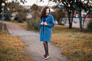 Fashionable young curly woman in autumn in park smiling wearing blue coat and red sneakers
