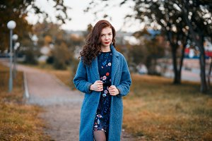 Fashionable young curly woman walking in autumn park wearing blue coat
