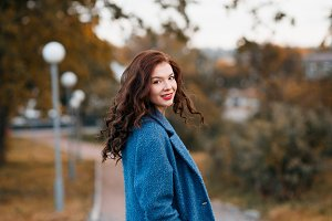 Fashionable young curly woman in autumn in park smiling and turning wearing blue coat