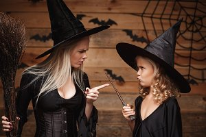 Halloween Concept - stressful witch mother teaching her daughter in witch costumes celebrating Halloween over bats and spider web on Wooden studio background.