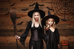Halloween Concept - cheerful mother and her daughter in witch costumes celebrating Halloween posing with curved pumpkins over bats and spider web on Wooden studio background.