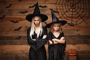 Halloween Concept - cheerful mother and her daughter in witch costumes disappointing with something.