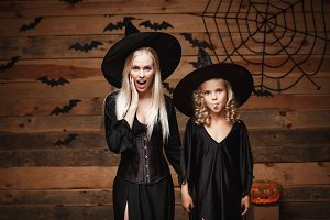 Halloween Concept - cheerful mother and her daughter in witch costumes shocking with something.