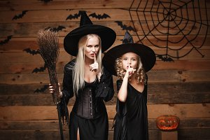Halloween Concept - cheerful mother and her daughter in witch costumes celebrating Halloween doing silence gesture posing with curved pumpkins over bats and spider web on Wooden studio background.