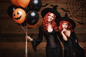 Halloween Witch Concept - cheerful mother and her daughter in witch costumes celebrating Halloween posing with orange and black balloon over bats and spider web on Wooden studio background.