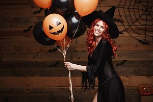 Halloween Witch Concept - Beautiful caucasian woman in witch costumes celebrating Halloween posing with posing with orange and black balloon over bats and spider web on Wooden studio background.