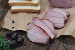 Piece of smoked Ham with some fresh herbs on wooden background