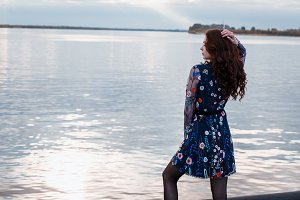 Young beautiful brunette woman in blue dress on the autumn river embankment