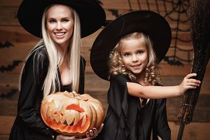 Halloween Concept - Closeup beautiful caucasian mother and her daughter in witch costumes celebrating Halloween posing with curved pumpkins over bats and spider web on Wooden studio background.