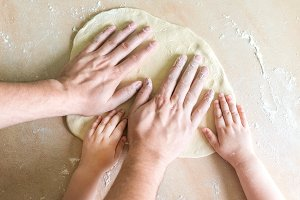 Children's and dad's hands on dough