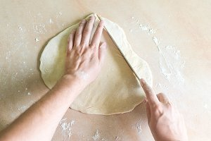 Men's hands cutting raw dough