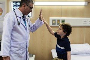 patient boy giving doctor hi-five