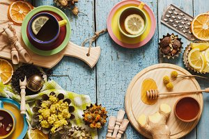 Cups with herbal tea and pieces of lemon, dried herbs and different decorations
