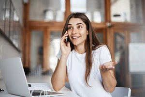 Young woman talking on phone positively surprised discovering her boyfriend is coming to town.
