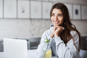 Young female student using a laptop between seminars to chat with her significant other. Drinking lemonade, smiling, dreaming of her holidays.