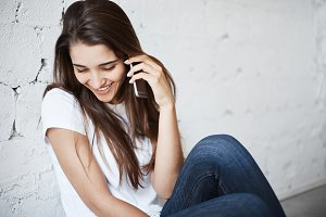 Young posh female using cell phone to call her significant other laughing smiling. Distant communications is a way to make relations stronger.