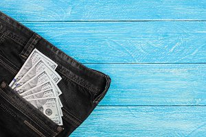 american dollar bills in jeans pocket on blue wooden background with copy space for your text. Top view