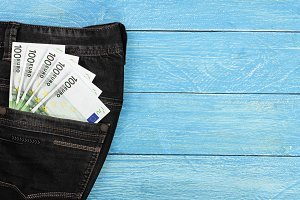 one hundred euro banknotes in a jeans pocket on blue wooden background with copy space for your text. Top view