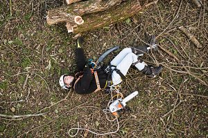 Injured lumberjack with chainsaw lying on the ground after fall
