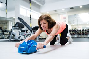 Senior woman in gym exercising abs with wheel roller