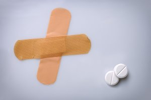 Two bandaids and two pills on table