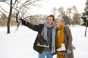 Senior couple in winter nature with ice skates going to rink.
