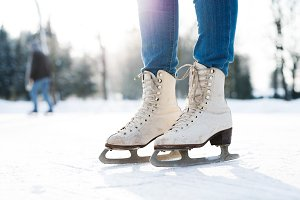 Legs of unrecognizable woman ice skating outdoors, close up.