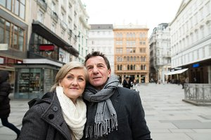 Beautiful senior couple on a walk in city centre. Winter.
