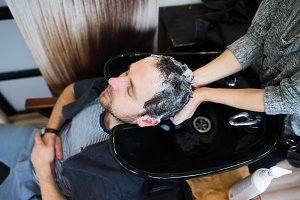 Professional hairdresser washing hair to her handsome client.
